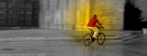 Man cycling past the Seu at night, Valencia, Spain