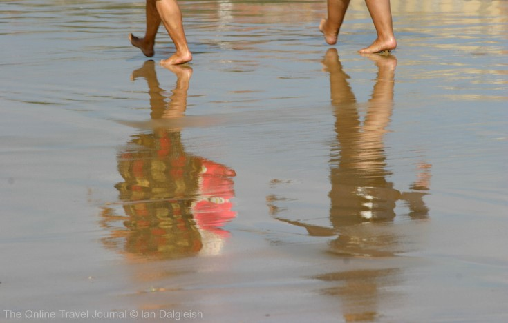 Reflections of beach walkers, Gijon, Asturias, Spain